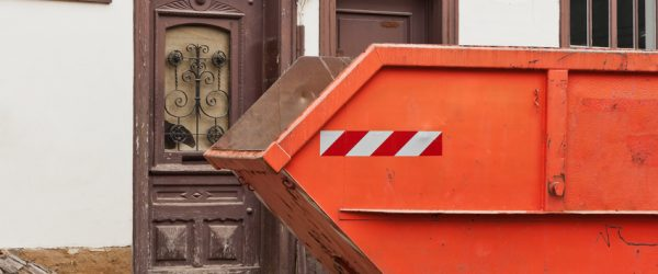 Ein grosser oranger Container fr Abfall vor einem alten Haus
