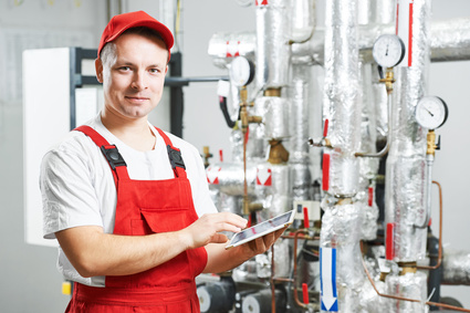 Technician maintenance repairman engineer inspecting heating system in boiler room